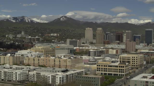vídeos de stock, filmes e b-roll de aerial view of urban cityscape near mountain range / salt lake city, utah, united states - mais zoom