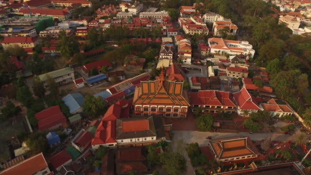 vídeos y material grabado en eventos de stock de aerial view of urban landscape in cambodia, featuring a traditional cambodian temple and dozens of red rooftops of the village houses - cambodia