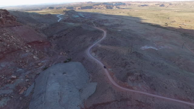 aerial view of vehicle moving on road in desert, drone following van on barren landscape - moab, utah - moab utah stock-videos und b-roll-filmmaterial