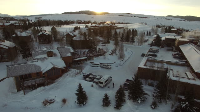 aerial view of vehicles amidst snow covered buildings in town, drone moving backward over town during sunset - jackson, wyoming - wyoming stock videos & royalty-free footage