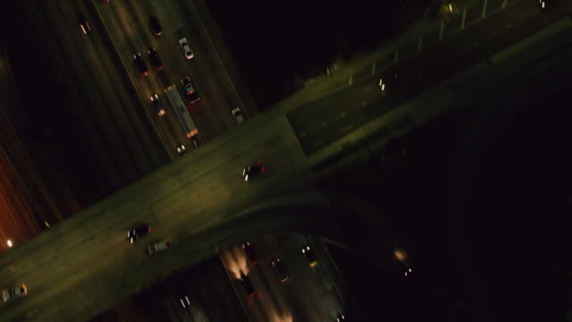 ws aerial view of vehicles driving on highway at night - road marking stock videos & royalty-free footage