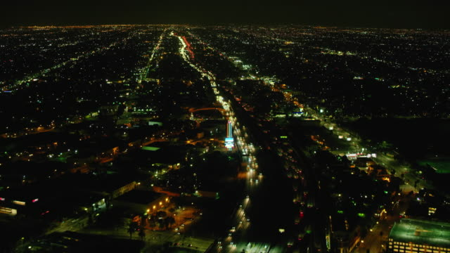 ws aerial view of vehicles driving on highway in city at night - parking stock videos & royalty-free footage
