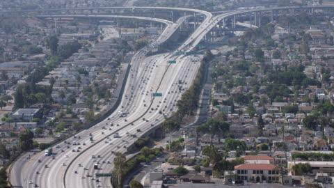 ws aerial view of vehicles driving on highway passing through suburban neighborhoods - urban sprawl stock videos & royalty-free footage