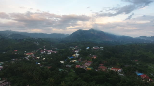 aerial view of village in anilao and mountain in the background - filippine video stock e b–roll
