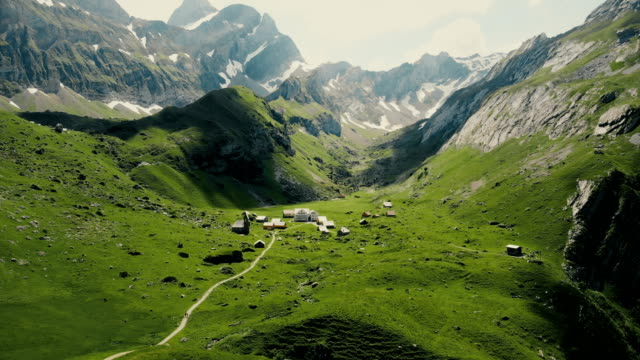 aerial view of village in mountains in switzerland - alpi video stock e b–roll