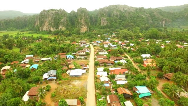 aerial view of village with limestone mountain at noen maprang in thailand - limestone stock videos and b-roll footage
