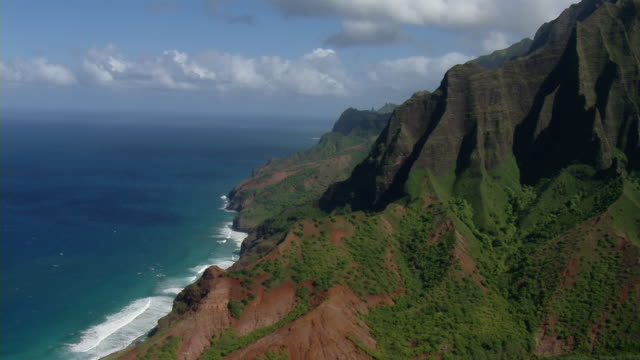 aerial view of volcanic coastal mountains in na pali coast state park on the hawaiian island of kauai. - na pali coast state park stock videos & royalty-free footage