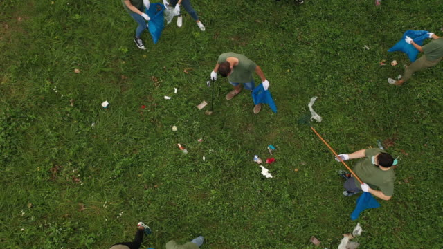 aerial view of volunteers cleaning public park together - matching outfits stock videos & royalty-free footage