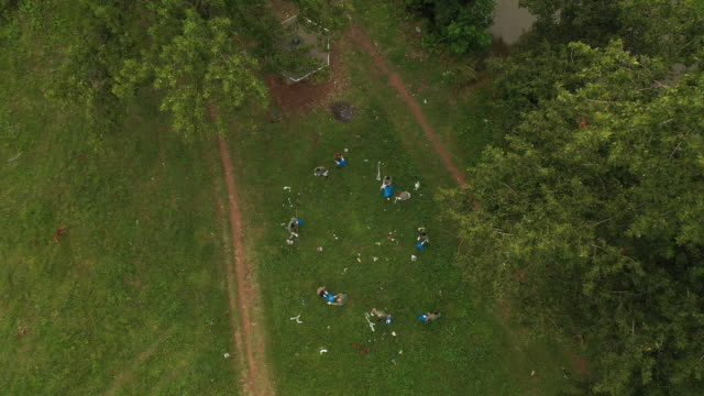 aerial view of volunteers picking up garbage while cleaning public park - matching outfits stock videos & royalty-free footage