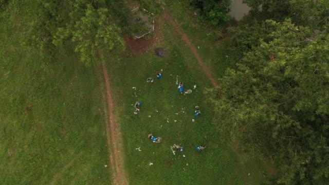 luftaufnahme von freiwilligen, die müll abholen, während sie den öffentlichen park reinigen - gartenhandschuh stock-videos und b-roll-filmmaterial