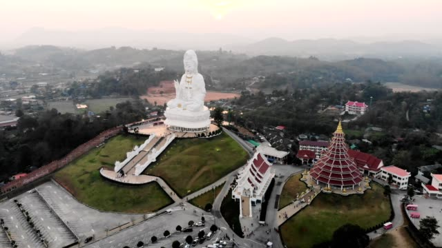 aerial view of wat huay pla kang with guanyin statue with buddhist temple on hill in evening at chiang rai - guanyin bodhisattva stock videos & royalty-free footage