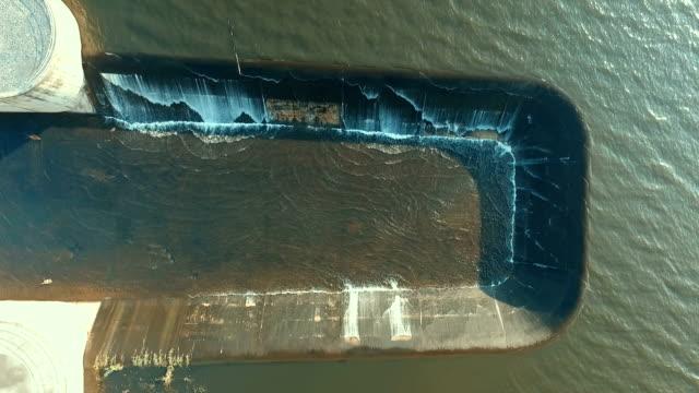 vídeos de stock, filmes e b-roll de vista aérea do estouro de respingo de água no velho rio lago barragem. - drenagem
