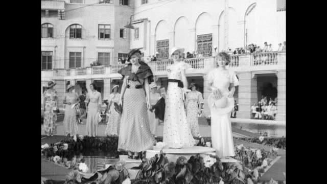 Aerial view of waterfront fashion show with models walking around runway as seated onlookers watch / models climb up on pedestals model dresses /...