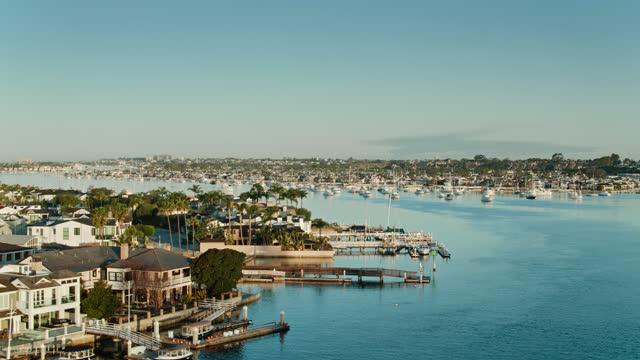 vidéos et rushes de vue aérienne des résidences de bord de mer avec des bateaux amarrés à newport beach, la californie - mar