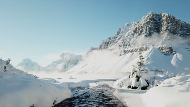 aerial view of waterfront with snow in winter, bow lake - montagne rocciose video stock e b–roll