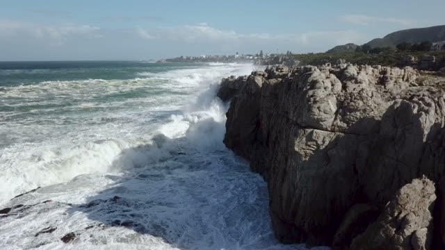 aerial view of waves crashing into a rocky shore - largo descrizione generale video stock e b–roll