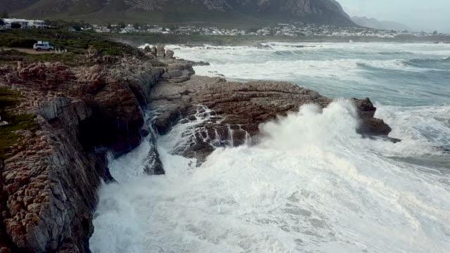 vídeos de stock e filmes b-roll de aerial view of waves crashing into a rocky shore - pedra rocha