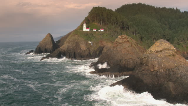aerial view of waves crashing on rocks below heceta head lighthouse. - heceta head stock videos & royalty-free footage