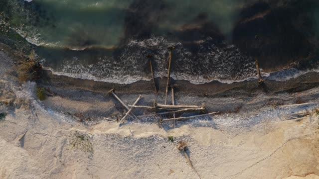 stockvideo's en b-roll-footage met luchtfoto van de golven op de oever met drijfhout - drijfhout