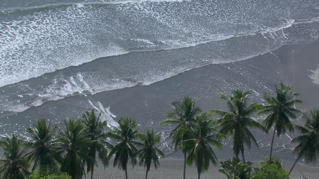 aerial view of waves crashing on tamales beach in puntarenas province, costa rica. - puntarenas province stock videos & royalty-free footage