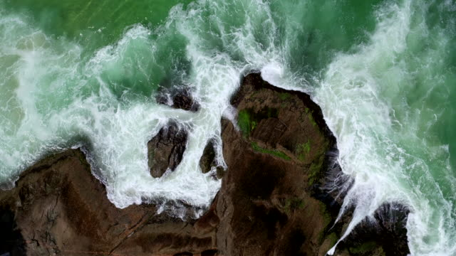 Aerial view of waves crashing on the rocks.