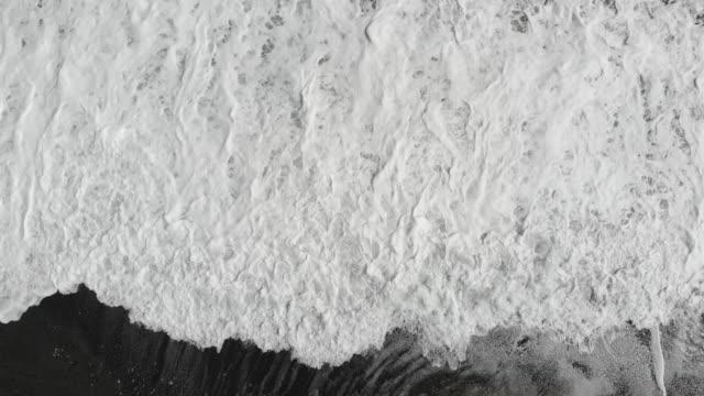 aerial view of waves crashing onto black sand beach - black sand stock videos & royalty-free footage