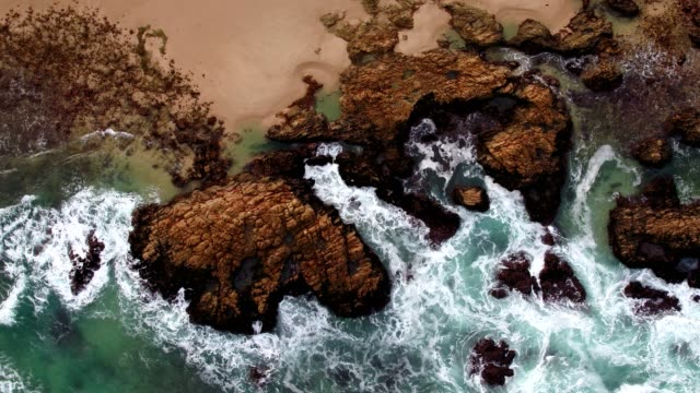 aerial view of waves crashing onto the rocks near the beach - eroded stock videos & royalty-free footage
