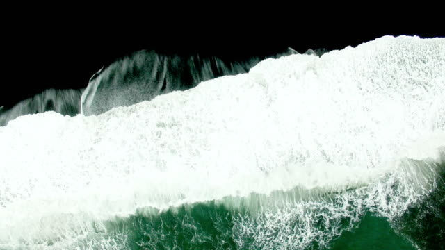 aerial view of waves on black sand beach in iceland - land stock videos & royalty-free footage
