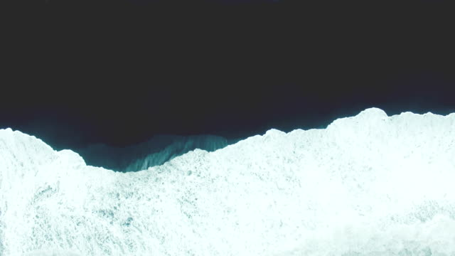 aerial view of waves on black sand beach in iceland - riva dell'acqua video stock e b–roll