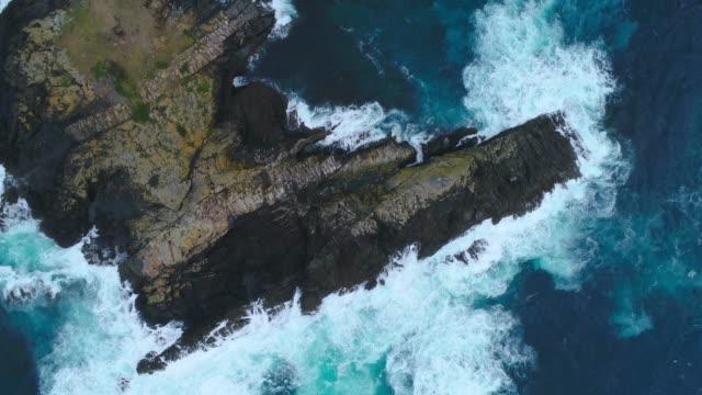 vidéos et rushes de vue aérienne des vagues éclaboussant dans la mer. - écume