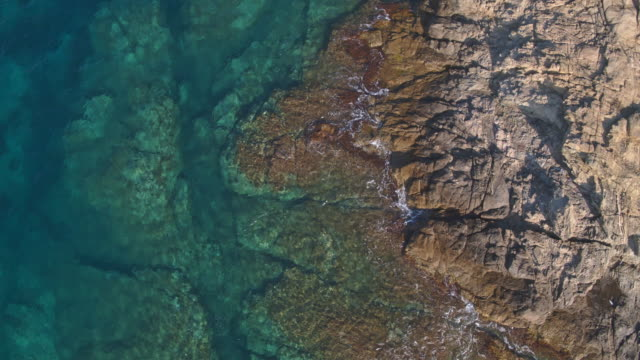 aerial view of waves towards rocky shore - rock formation stock videos & royalty-free footage
