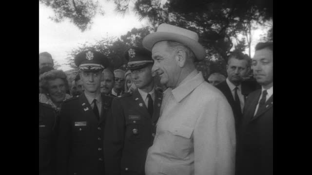 aerial view of wellington new zealand / president lyndon b johnson shakes hands with crowd through chain link fence / motorcade drives down crowded... - präsident der usa stock-videos und b-roll-filmmaterial