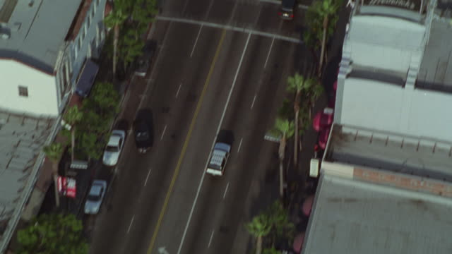 stockvideo's en b-roll-footage met aerial view of west los angeles. camera moves down hollywood blvd. roosevelt hotel, grumman's chinese theater, ripley's believe it or not. office and apartment buildings. palm trees line sides of street. traffic and cars on street. pedestrians crowd sidew - boulevard