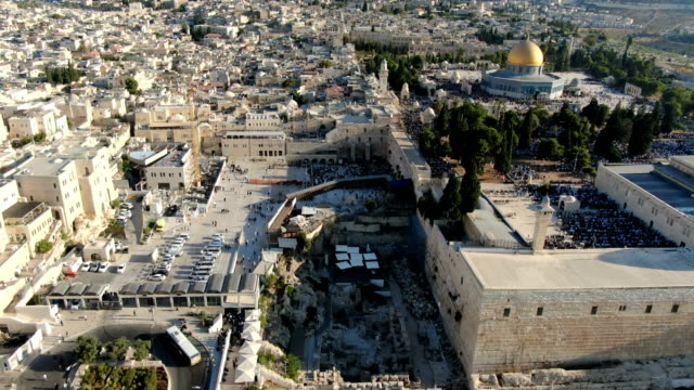 aerial view of western wall in the old city of jerusalem, with dome of the rock, al-aqsa mosque and thousands of jewish and muslim prayers - jerusalem stock-videos und b-roll-filmmaterial