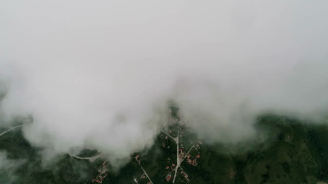 Aerial view of white low clouds moving over green hills of a mountain village.