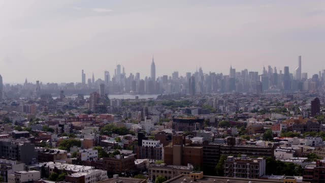 vídeos de stock, filmes e b-roll de aerial view of williamsburg neighborhood in view of manhattan skyline in brooklyn new york - williamsburg new york