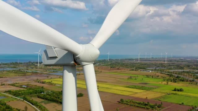 aerial view of wind turbine(renewable energy) nearly the beach/rice field at south of thailand with cloudy sky - blade stock videos & royalty-free footage