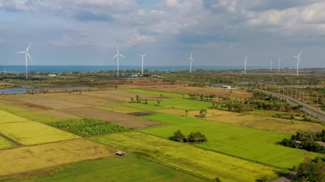 aerial view of wind turbine(renewable energy) nearly the beach/rice field at south of thailand with cloudy sky - turbine stock videos & royalty-free footage