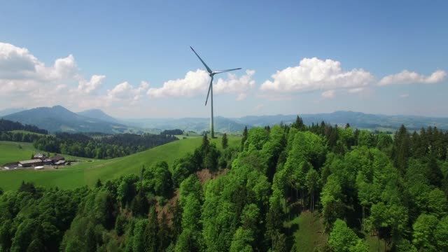 aerial view of wind turbine standing on hill top - turbine stock-videos und b-roll-filmmaterial