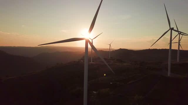 vídeos de stock, filmes e b-roll de vista aérea das turbinas eólicas com energia alternativa ao nascer do sol - energia eólica