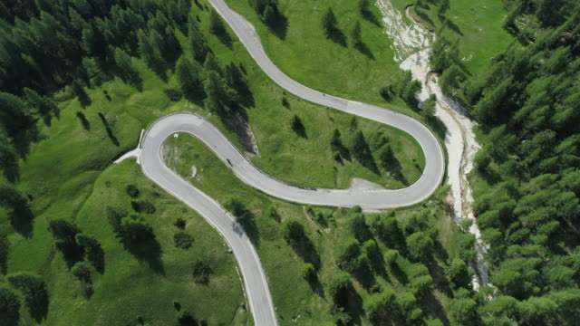 aerial view of winding road with hairpin with driving motorcycle, falzarego pass. falzarego pass, dolomites, belluno province, veneto, italy, european alps, europe. - winding road stock videos & royalty-free footage