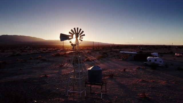aerial view of windmill and trailers on desert farm at sunset - remote location stock videos and b-roll footage