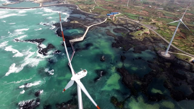 vidéos et rushes de aerial view of windmills beside shinchang coastal road (famous for beautiful coastline road and wind turbines in jeju) - vert