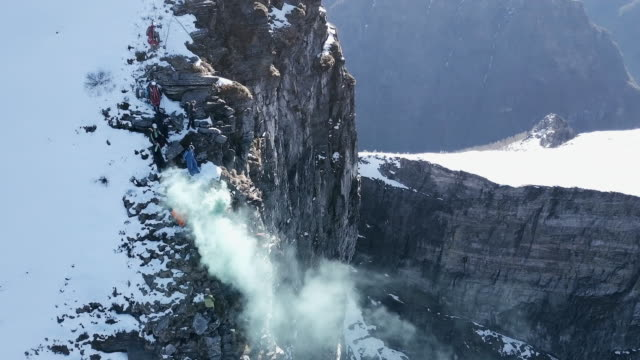 aerial view of wingsuit pilot jumping off alpine cliff - medium group of people stock videos & royalty-free footage
