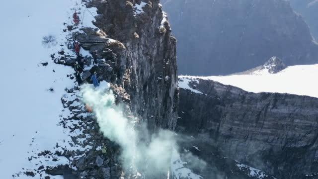 luftaufnahme des wingsuit pilot von alpine klippe zu springen - klippe stock-videos und b-roll-filmmaterial
