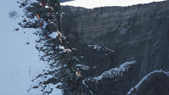 Aerial view of wingsuit pilot jumping off alpine cliff
