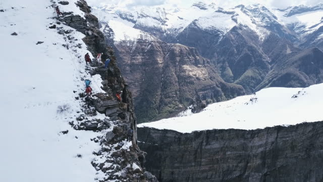 Aerial view of wingsuit pilots jumping off alpine cliff