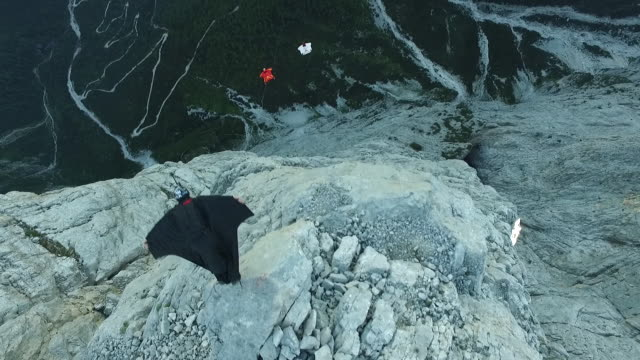 Aerial view of wingsuit pilots jumping off cliff