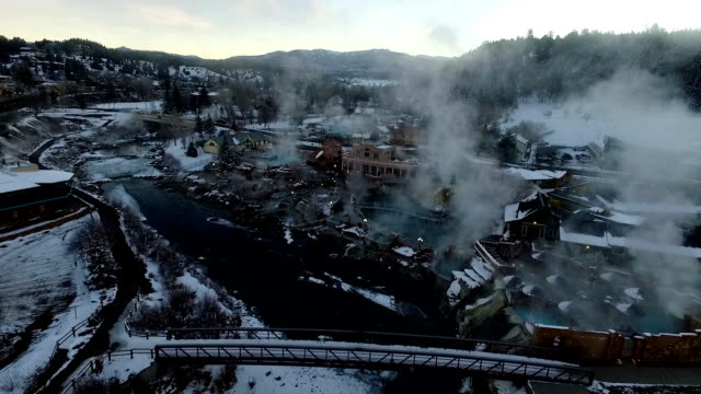 Aerial View of Winter Wonderland Pagosa Springs Colorado Bridge over San Juan River Hot Springs Steam Lifting Winter Snow Covered Rocky Mountains with nice Motion Pan
