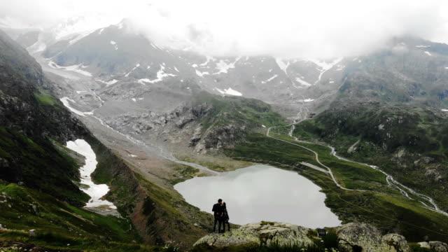 vidéos et rushes de vue aérienne de la femme et l'homme près du lac dans les alpes suisses - alpes suisses